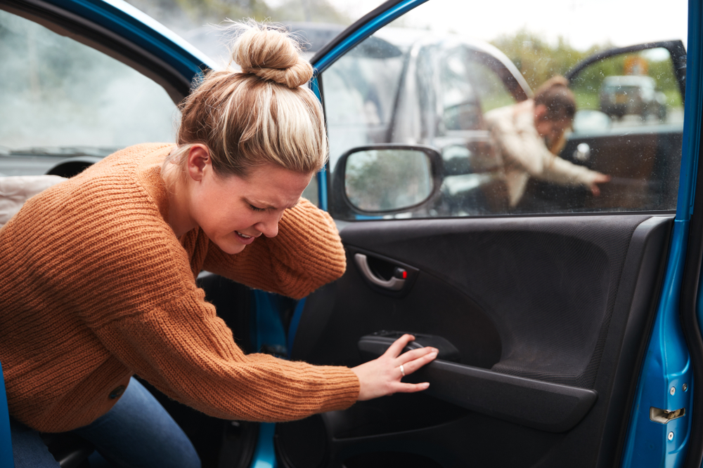 woman with personal injury from care accident getting out of car